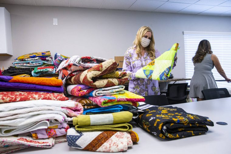 Tennille Pereira, director of the Vegas Strong Resiliency Center, looks through donated quilts ...