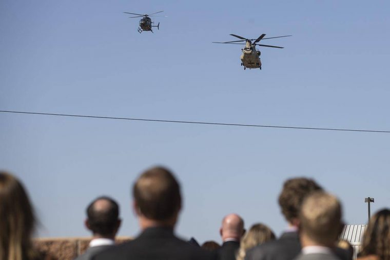 A Chinook and Lakota helicopters conduct a fly over before the start of a ceremony to honor the ...