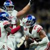 New York Giants running back Saquon Barkley (26) celebrates his touchdown in overtime with wide ...