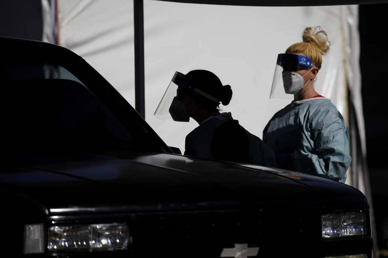 FILE - In this July 10, 2020, file photo, healthcare workers test patients in their cars at a d ...