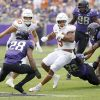 Texas running back Bijan Robinson (5) carries the the ball as a host of TCU defenders close in ...